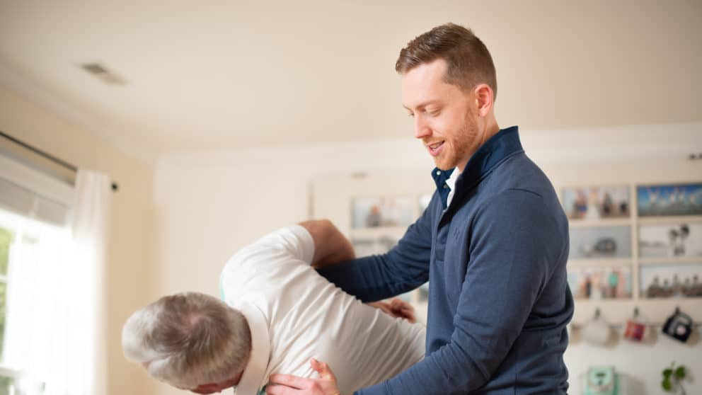 Physical therapist working on older mans back and shoulders